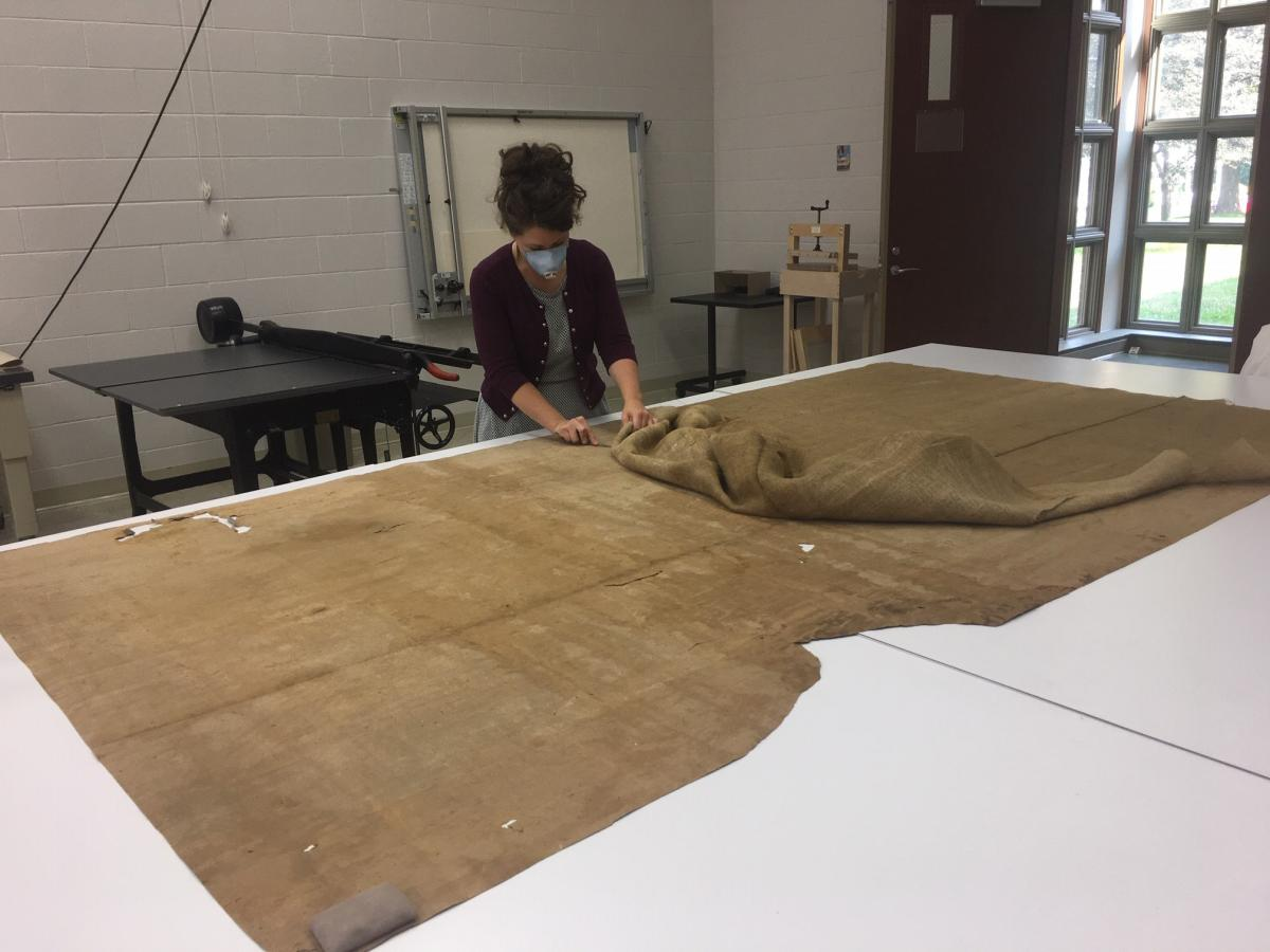 Conservator removes burlap from back of mural