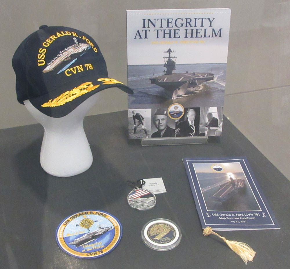 Hat, books, medal, and patch commemorating the commissioning of the USS Gerald Ford in display case.