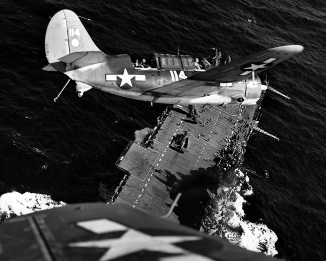 A Curtiss Helldiver circles above an aircraft carrier in the South Pacific, January 1945. U.S. Navy photo, 80-G-320999