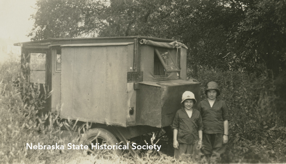 "Two girls stand beside ""Uncle John's motor home,"" circa 1930"