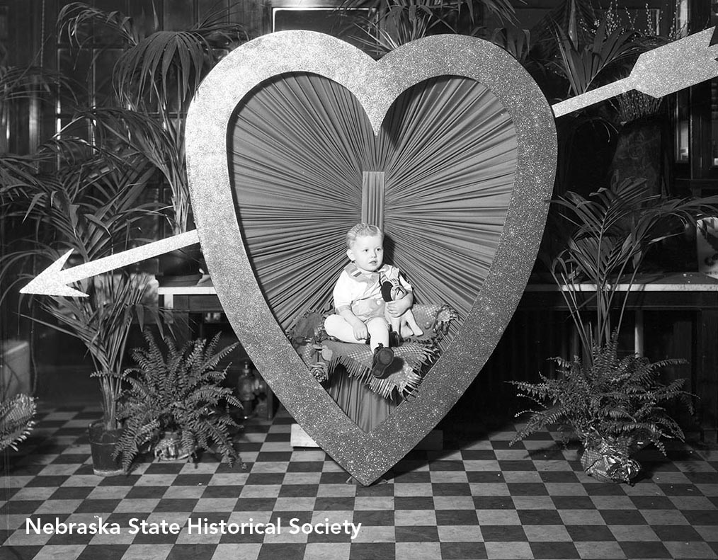 A Valentine's Day portrait of a child sitting in a large heart with an arrow through it, Omaha 1934